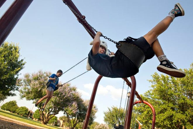 Halo Turner and her younger sister, Annabelle, see who can swing the highest at Crescent Park in Frisco.