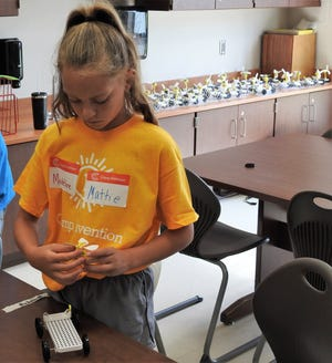 Fourth-grader Mattie Thomas works on a morphing car with other models behind her on a counter top during Camp Invention at Coshocton Elementary School.