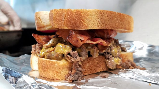 Texan sandwich with thinly sliced steak, cheddar cheese and bacon on Texas toast in the Poppa Bacon's Street Kitchen truck on Wednesday, June 30, 2021.
