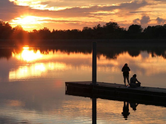 A couple of people enjoy some fishing during a picturesque sunset at Fremont reservoir. The weather projections will cooperate for more fishing and outdoor living in the next few days, according to the National Weather Service. Today is to be mostly clear, and the forecast for Saturday and Sunday is mostly sunny, with a high of 88 on Independence Day.