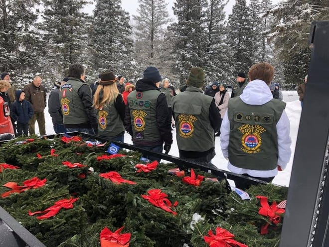 These members of AMVETS Post 127 helped lay remembrance wreaths on the graves of 60 veterans at the Village of Ingram Cemetery.