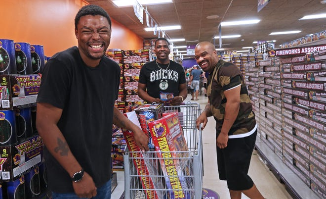 Terry Walters, left, Jonathon McCray, center, and Quamay Daniels, all from Kenosha, show off their fireworks purchases at Phantom Fireworks of Racine. They said lighting fireworks at their homes is a family tradition. They were also planning on going to Extreme Fireworks a few miles away.