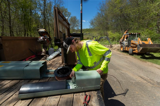 Eau Claire-based Underground Systems Inc. employee Derrick Yarrington assembles a pedestal for a project burying fiber optic cable in Hager City. The project was partially funded by a $444,211 state public service commission grant to Hager Telephone Co.