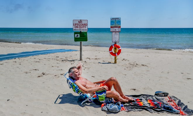 """A beachgoer who didn't want to be identified sunbathes in front of a """"No Lifeguard on Duty"""" sign Thursday, July 1, 2021, at Bradford Beach in Milwaukee."""