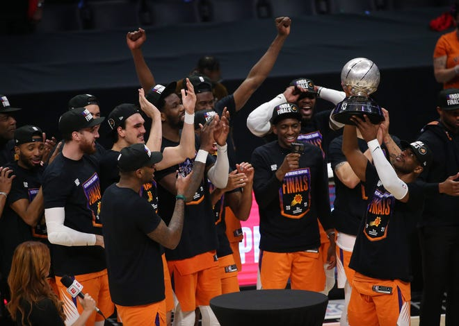 Phoenix Suns guard Chris Paul (3) lifts the Western Conference trophy after defeating the LA Clippers in Game 6 at the STAPLES Center June 30, 2021.