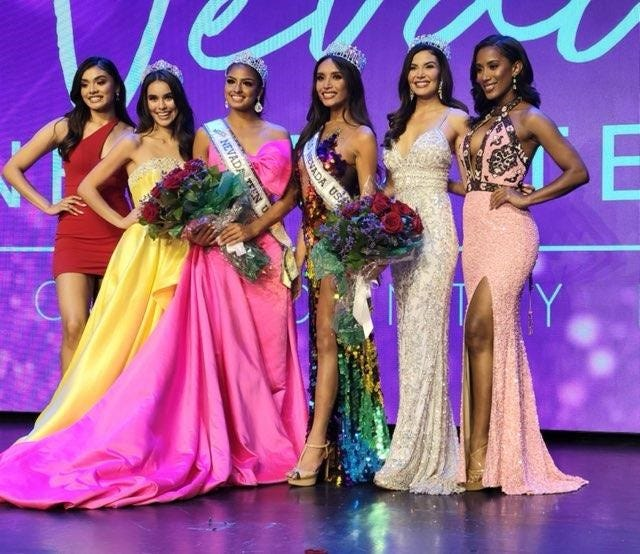 A photo of Kataluna Enriquez (fourth from left) and others posing for a photo.  Enriquez was the first transgender woman to be crowned Miss Nevada USA.