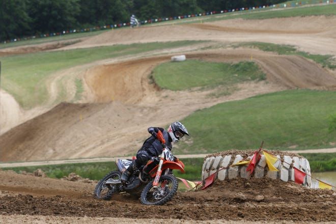 A rider takes a turn at Grear's Motorsports Park in Zanesville. Some of the 1.1 main track can be seen draped across the hills behind him.