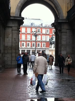 A local heads home with groceries in Madrid's busy Plaza Mayor. By Kitty Bean Yancey, USA TODAY