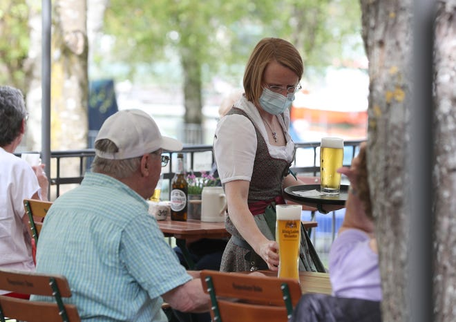 A waitress serves beer at a beer garden on May 10, the first day that outdoor restaurant seating reopened in some regions across Bavaria in Woerthsee, Germany.  (Photo by Alexandra Beier/Getty Images)