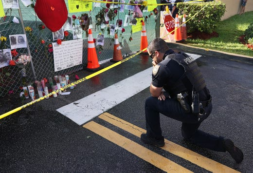 Miami Beach police officer, David Cajuso, prays before a memorial setup near the partially collapsed 12-story Champlain Towers South condo building on July 01, 2021 in Surfside, Florida.