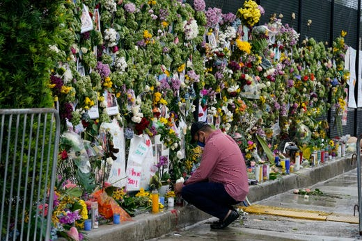 Local resident Louis Thompson, who is missing friends in the collapse of Champlain Towers South, kneels in front of a makeshift memorial to the scores of people who remain missing or were killed, nearly a week after the condo building partially collapsed, Wednesday, June 30, 2021, in Surfside, Fla.