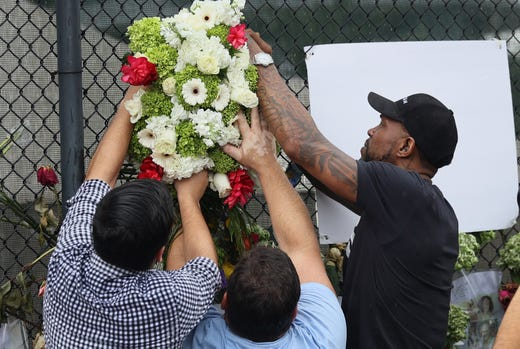 SURFSIDE, FLORIDA - JUNE 30: Udonis Haslem (R), from the Miami Heat basketball team, places flowers at a memorial to those missing from the partially collapsed 12-story Champlain Towers South condo building on June 30, 2021 Surfside, Florida. Over one hundred people are reported as missing as the search-and-rescue effort continues.  (Photo by Joe Raedle/Getty Images) ORG XMIT: 775671250 ORIG FILE ID: 1326314381