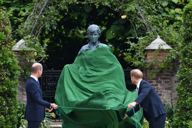 Britain's Prince William, left, and Prince Harry unveil a statue they commissioned from their mother Princess Diana on Thursday on what would have been her 60th birthday in Kensington Palace's Sunken Garden in London.