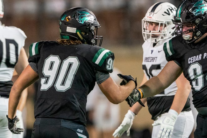 Cedar Park defensive end Ian Ferguson, left, and defensive tackle Murray Robinson celebrate stopping a Vandegrift drive during a game last season. The all-district duo anchors the top defensive line in the district.