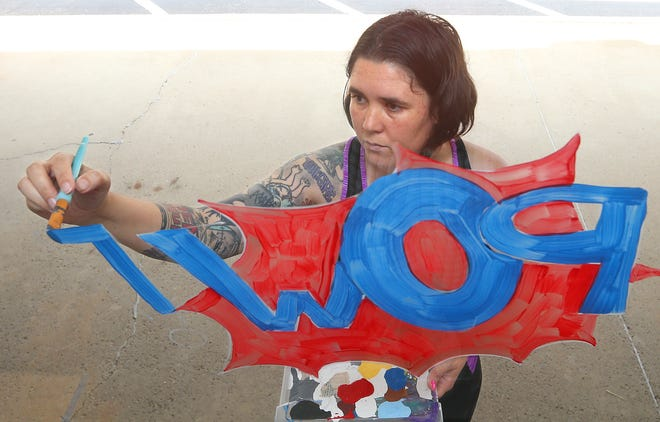Artist Leila Griffiths paints her work on the window at Blue Wolf Martial Arts studio Thursday at the Shoppes of Stow.