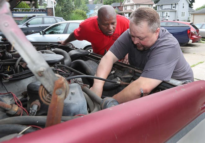 Harvey Bryant, left, founder of Miracle on Wheels, and Bill Harrison, owner of KB Automotive Technologies, look over the engine of a truck Thursday in Cuyahoga Falls. Harrison is donating free labor to Bryant's program.