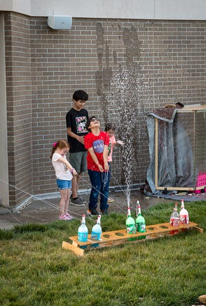 """Adrian Ortiz takes advantage of the fountain of soda he helped create at the Don Harrington Discovery Center during the annual """"Explode"""" event featuring science experiments that explode for the family."""