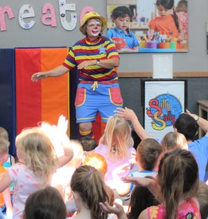 Silly Sally performs for a group of children.
