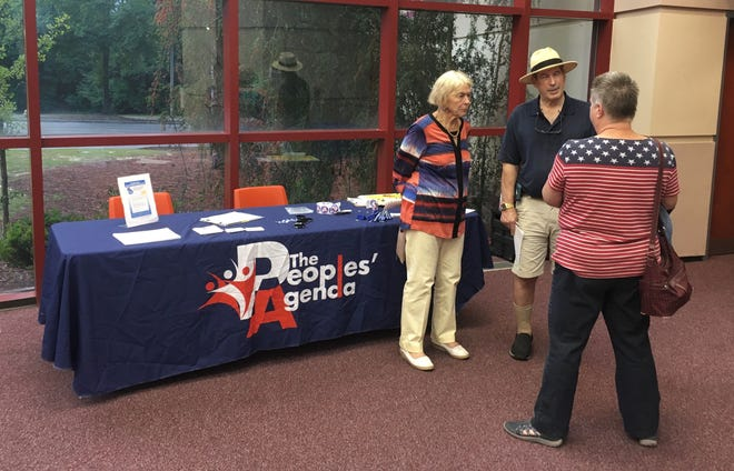 Gay Keesee, right, field organizer for The People's Agenda, talks to two attendees after the presentation Thursday.