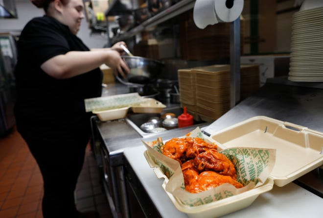 Chicken thighs are prepared by Susan Siders at Wingstop. With the price of chicken wings rising due to a nationwide shortage, Wingstop is using the name Thighstop to sell the cheaper chicken option through its website and via Doordash delivery.