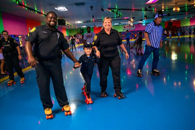 Senior Officer Travonte Kitchen and Sgt. Kim Stewart skate with a boy around the rink at Roll With Patrol on Tuesday. [Cindy Peterson/Correspondent]