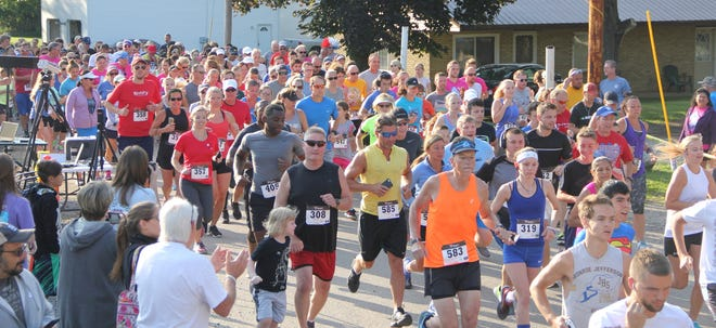 A large group of runners heads through the streets of Manitou Beach during a previous year's edition of the Devils and Round Lake Men's Club Firecracker 7K run/walk fundraiser. The 10th anniversary of the patriotic-themed run is scheduled for Sunday, July 4, at the Highland Inn, 3171 Round Lake Highway.