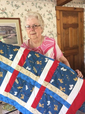 Pauline Dwelly shows one of her baby quilts.