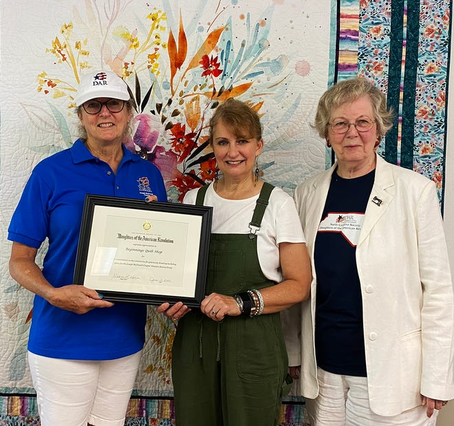 From left, Sharon Horan presents a certificate of appreciation to Kathy Neal, co-owner of Beginnings Quilt Shop, for its service to veterans. Jay Mizeras is the Veterans Sewing Group chairman.