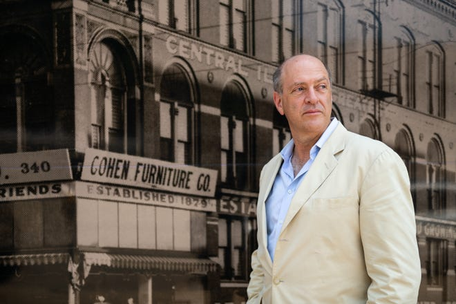 Les Cohen stands in front of a historic photo of the Cohen Furniture Company on Thursday, July 2, 2021. Cohen, who nows runs a development company, plans to renovate the building to its former glory, including restoring the large windows and making the building environmentally friendly.