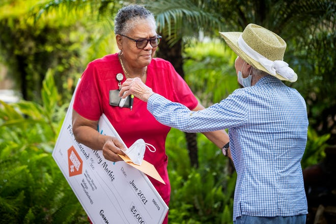 Mary Mathis, left, a CNA at Florida Presbyterian Homes is congratulated by resident Jeannette Swain after receiving a $5,000 prize during a brief ceremony in the courtyard at the nursing home in Lakeland on Friday. Mathis won a national Gannett contest. She has been a CNA at Florida Presbyterian Homes for 45 years.
