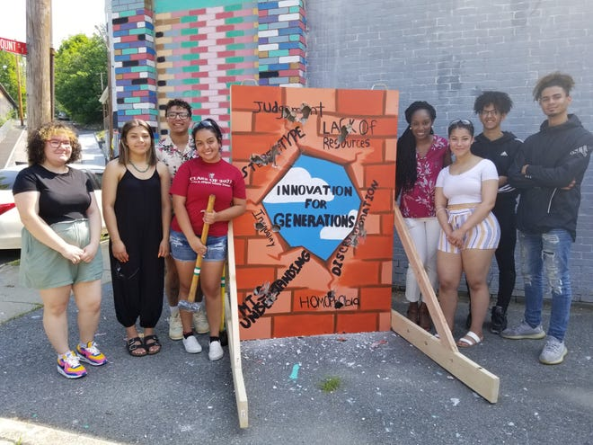 """Youth Founders stand with Director of Youth Programs Shana Fitz, fourth from left, beside their mural """"wall"""" that represents breaking the barriers in their lives."""