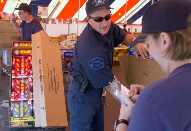 In this Monroe News file photo, Sgt. Melinda Logan takes down the type and number of fireworks from state police officers as they line up with cartfulls of Class B illegal fireworks in a tent near Flat Rock.  The fireworks from at least eleven tents dotting Telegraph south of Flat Rock were loaded onto trucks to be confiscated and later detonated safely, leaving only the legal sparklers and fountains. Enforcement tactics like these have been out-of-date since 2011, when Michigan law changed to allow residents to legally purchase virtually any type of fireworks.