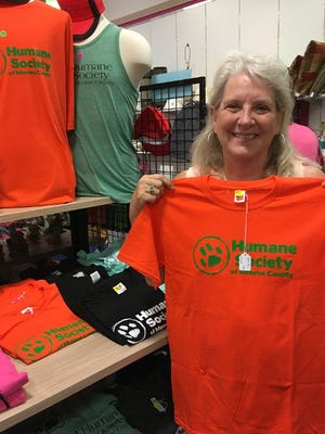 Madonna Burkit, executive director of the Humane Society of Monroe County, holds a Humane Society shirt at the society's Thrift Store, which is located in the Mall of Monroe. In September, 2019, the Thrift Store moved to a more visible location in the mall, near the Phoenix Theatre, Spencer's and Bath and Body Works. The store sells toys, books, home items, artwork, dishes and pet items. Specials are offered each month. Donations are accepted. Clothing and outdated electronics are not accepted.