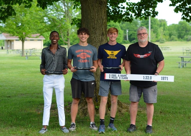Butch Roupe (right) set a New Boston Huron school record in the 800-meter relay in 1971 that stood for 50 years before it was broken by a team that included (left to right) Antonio Talley, Caleb Henninger and his grandson, Ayden Roupe. Isaac Smith, the fourth member of the relay, was not present for the photo.
