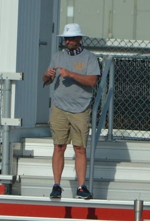 Jefferson girls track and field coach Phil Speare checks splits for his relay runners during the Regional meet at Milan. Speare has been named Monroe County Region Girls Track and Field Coach of the Year.