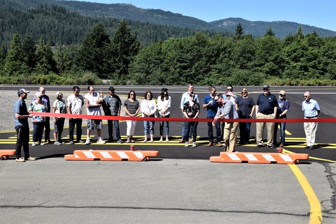 After 6 years, completing the $3.2 million Mott Airport project, Dunsmuir City staff, County Supervisor Ed Valenzuela, Dunsmuir Council members, representatives from the Siskiyou County Transportation, past and current City Managers Randy Johnson and Todd Juhasz, Carol Ford with Ford and Associates,LLC. and Kimley Horn Associates that managed the project, LaMafa representative Erin Ryan, retired pilots and volunteers Dr. Ed Miller and Jerry Denham cheer Mayor Matthew Bryan as he cuts the red ribbon at last Wednesday's  ceremony to the new Dunsmuir Mott Airport runway.