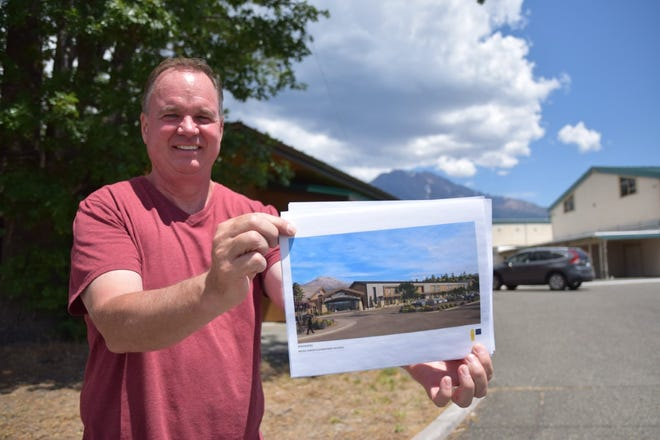 Weed Elementary School principal/superintendent Jon Ray stands in front of his campus with a rendering of how the school will look from the same spot after it is rebuilt. The school will be torn down and rebuilt due to health risks found in the buildings last year.