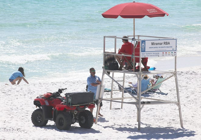 A Beach Ambassador speaks recently with a lifeguard in Miramar Beach. Walton County officials, in conjunction with local accommodation providers and other tourist-related businesses, are working to increase beach safety awareness.