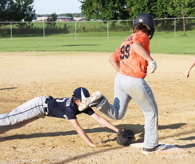 Dewald Construction batter Ben Melchers nips a diving Pontiac Police Association first baseman Cale Christenson to the first base bag for a hit in the opener of the Little League City Series Thursday at the Rec-Plex. Dewald Construction rallied for a 17-16 win.