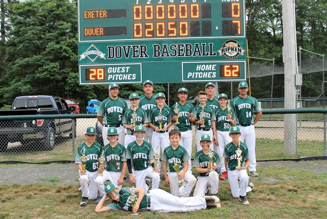 Dover players and coaches show off their hardware after defeating Exeter in the championship game of the East Area Cal Ripken 12U 70-foot tournament Thursday night in Dover.