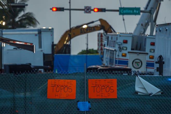 """""""Deja que los temas mexicanos te ayuden"""" La señalización se cuelga el viernes 2 de julio de 2021 en el sitio del colapso del edificio Champline Towers South en Surfside, Florida.  Los esfuerzos de búsqueda y rescate continúan en la segunda semana."""