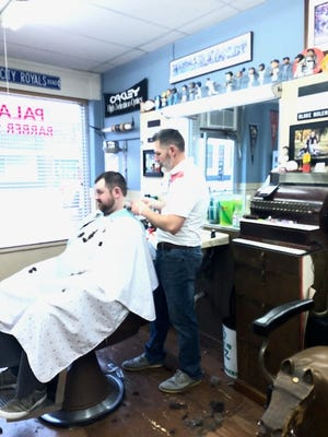 Bake Bolen, owner of Palace Barber Shop, gives a customer a hair cut.