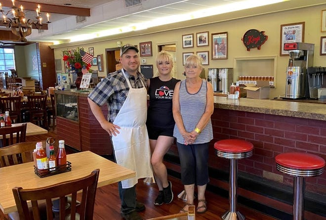 From left to right, Matthew Keeler, co-owner Alicia Keeler, and co-owner Joan Hawks pose for a photo in the King's Famous Barbecue dining room in June of 2021.