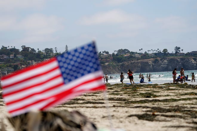People walk along La Jolla Shores beach as Independence Day weekend nears in San Diego. Holiday travel over the Independence Day weekend is expected to nearly return to pre-pandemic levels, according to AAA.