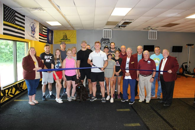 Holding the scissors is Primal Athletic Co. gym owner and operator, Jackson Mitchell.