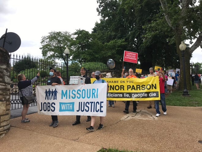 Demonstrators march past the Governor's Mansion in Jefferson City on Thursday, July 1, 2021. Protesters gathered on the day more than 275,000 Missourians would have been eligible to enroll in Medicaid expansion if it had gone into effect. Photo by Tessa Weinberg/Missouri Independent