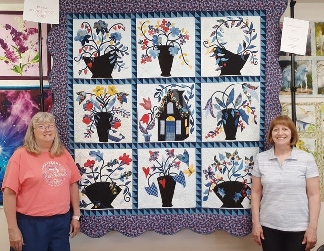Pictured with the displayed quilt are two of the quilt's creators, Terri Welch and Sharoll Stuckey.