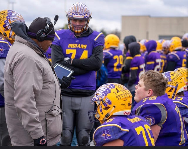 Hononegah offensive line coach Andy Trice, who is battling cancer, is shown instructing his players during a game.