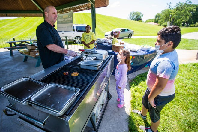 Chef Kenneth Acosta serves grilled fruits and vegetables for Eli Alpizar and Francheska McMichael during the Discovery Kitchen event Friday at the Charles Black Community Center in South Bend.