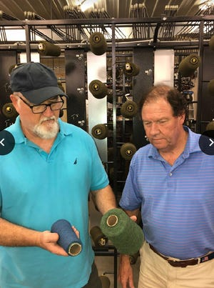 John Gage, left, and Mike Hawkins look over fabrics at the facility in Kings Mountain.